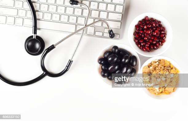Top View healthy food concept shot with stethoscope, keyboard, fruits