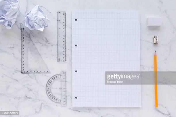 top view marble desk with graph paper and maths eq