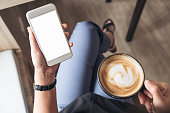 Top view mockup image of a woman's hand holding white mobile phone with blank desktop screen while drinking coffee in cafe