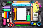 Top view of a large group of multi colored school or office supplies shot on rustic black background. A blank note pad is at the center of the composition with a useful copy space ready for text and/o