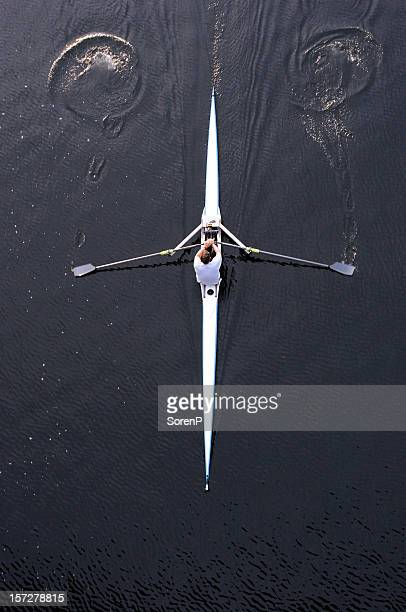 Top view of a man rowing his boat on dark water