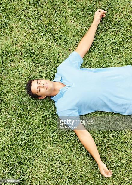 トップの若い男性のリラックスに最適な芝生