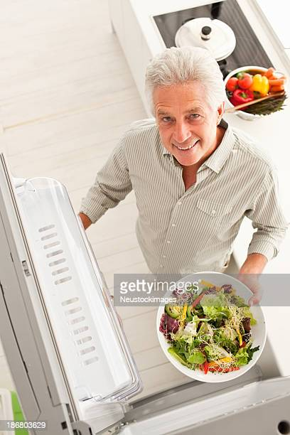 Top view of an elderly man with a salad dish