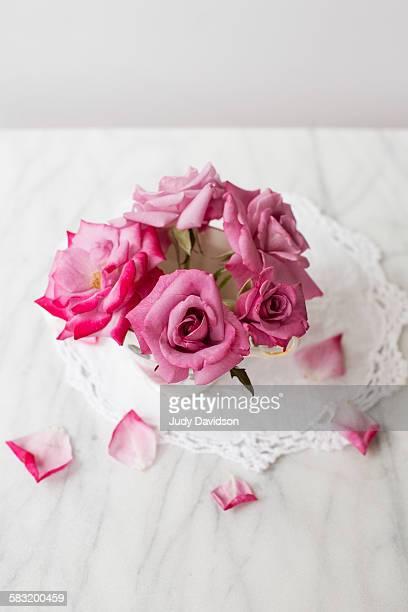 top view of arrangement of pink roses in teacup