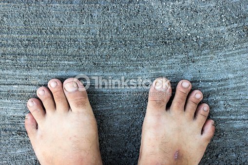 Top View Of Bare Foot On Cement Floor Background Stock Photo