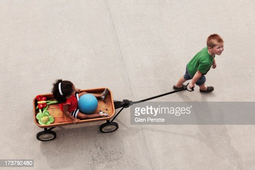 Top view of boy pulling girl in red wagon