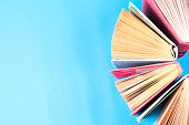 Top view of colorful hardback books in a circle. Open book, fanned pages, free copy space. Back to school copy space. Education background.Top view of colorful hardback books in a circle. Open book, f