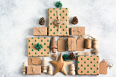 Christmas concept, Christmas tree made of brown present boxes, pine cones, jute twine, wooden ornaments on the light background, top view, copy space for text
