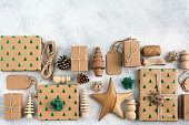 Christmas arrangement, brown present boxes with sparkling embossed fir trees, pine cones, wooden decorations, jute twine, top view, on the light background, copy space for text