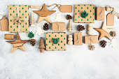 Christmas arrangement, brown present boxes with embossed fir trees, pine cones, brown gift tags, wooden decorations, jute twine, top view, on the light background, copy space for text