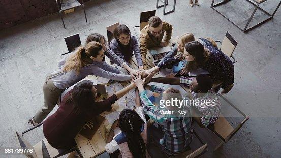 Vista superior del equipo de negocio trabajando en oficina de loft moderno. Grupo de jóvenes mestizos de personas reúne palm centro : Foto de stock