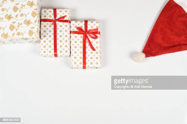 Top view of Christmas gift boxes on white table with Santa cap
