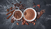 Top view of cocoa powder and chocolate chips in white bowls and whole cocoa beans with spices as ingredient for confectionery on black marble background