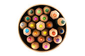 Top view of colorful wood pencils in a circle box isolated on white background.