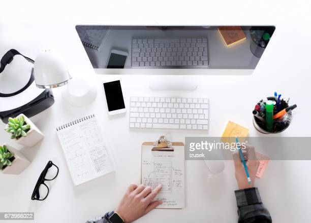 Top view of computer programmer sitting at the desk