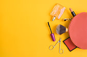 Top view of pink cosmetic bag consist of makeup brush, lipstick, brush on, scissors, mascara,  eyelash curler, and perfume on yellow background