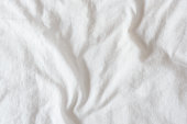 Top view of creased / wrinkles on a white unmade / messy bed sheet after waking up in the morning. Bedsheet is not neatly arranged for new guests or customers to sleep in. Abstract texture background
