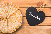 Top view of crepes (french pancakes), word chandeleur (meaning candlemas) written on a heart, rustic wood background