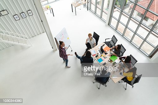Top view of diverse people of creative team group using smartphone, mobile phone, tablet and computer laptop while meeting. Overhead view of asian young creative start up meeting with wide angle view. : Stock Photo
