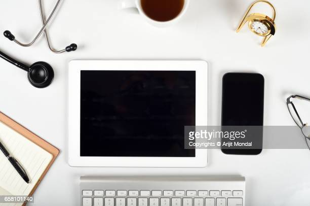 Top View Of Doctor Office Desk Table With Stethoscope And Lot Of Things, Copy Space