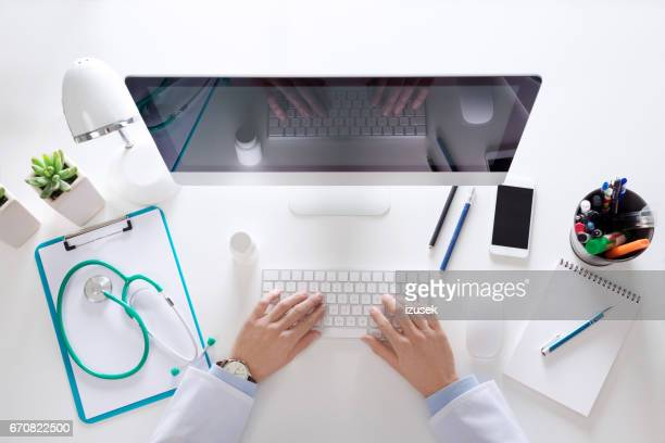 Top view of doctor sitting at the desk and using computer