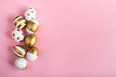 Top view of easter eggs colored with golden paint. Various striped and dotted designs. Pink background.