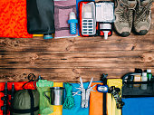 Top view of equipment for hiking and travel on wooden background with copy space . Items include trekking pole, multi tool, flashlight, hygiene products, tracking clothes