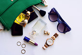Top view of female fashion accessories for woman. Stylish sunglasses, green bag , gold watch , lipstick , perfume , rings , smartphone