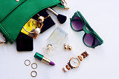Top view of female fashion accessories . Green hanbag with  sunglasses,  gold watch , lipstick , perfume , rings , smartphone