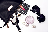 Top view of female accessories for woman. Trendy black sunglasses, black handbag , watch , lipstick , perfume , rings , smart phone