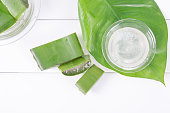 Fresh aloe vera leaves with aloe vera juice in glass bowl on wooden background