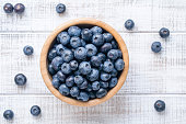 Bowl of fresh blueberries on vintage white background. Top view