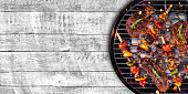 Top view of fresh meat and vegetable on grill placed on wooden floor. Barbecue, grill and food concept