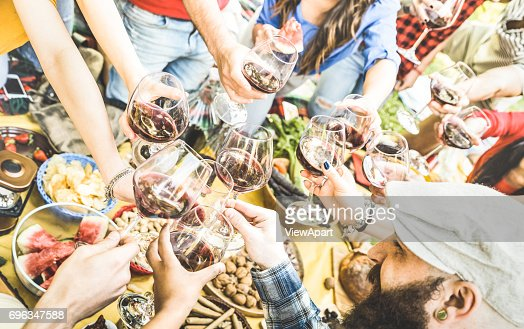 Top view of friend hands toasting red wine glass and having fun outdoor cheering at picnic winetasting - Young people enjoying summer time together at lunch bbq garden party - Youth friendship concept : Foto de stock