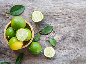 Top view of green lemon group and slice in bowl on wooden background with copy space