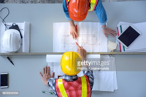 Top view of group of engineering team is meeting, planning construction work,looking paper plans at construction site,overhead view : Stock Photo
