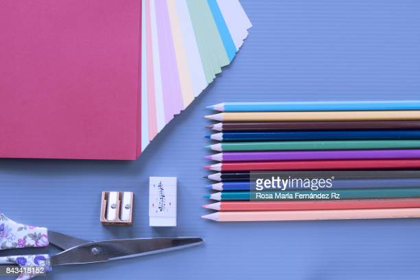 Top view of group of school or office supplies on blue background. Copy space for text and/or logo