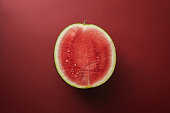 top view of half of watermelon on red surface