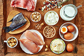Dairy, eggs, fish and meat, chickpea, beans and nuts on rustic wooden table.