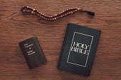 top view of holy bible with new testament and beads on wooden table