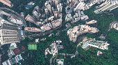 Top view or aerial shot of skyscrapers and green trees in a big city. Hong Kong, China.