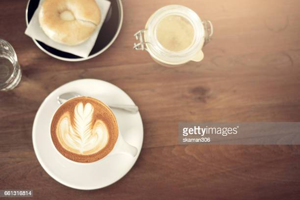 Top view of Hot coffee with milk and bread on wooden table