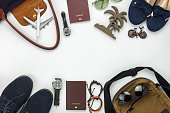 Top view of items for travel with fashion men & women background concept.Difference essential accessory on the white wood area.Copy space for creative font or text design.Objects for traveler on trip.