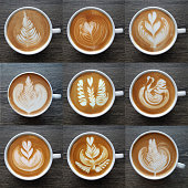 Collection of top view of  latte art coffee mugs on timber background.