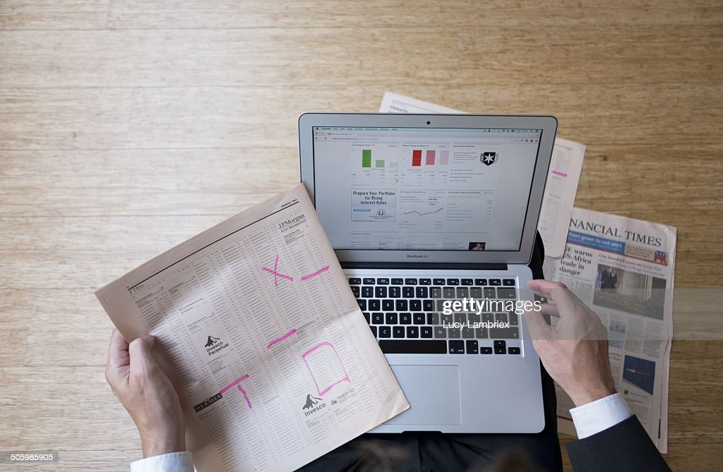 Top view of man reading financial times while checking online financial information on his laptop.