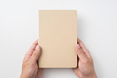 Design concept - Top view of man's hand holding hardcover kraft notebook isolated on white background for mockup