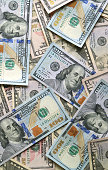 Top view of many United States one hundred dollar ($100) bills, vertical photo for background