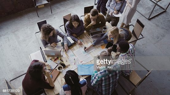 Top view of mixed race business team sitting at the table at loft office and working. Woman manager brings the document : Foto de stock