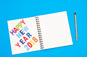 Top view of modern workplace with office supplies on blue background. Flat lay design and happy new year 2018 words