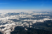 Top view of mountains with river and clouds.
